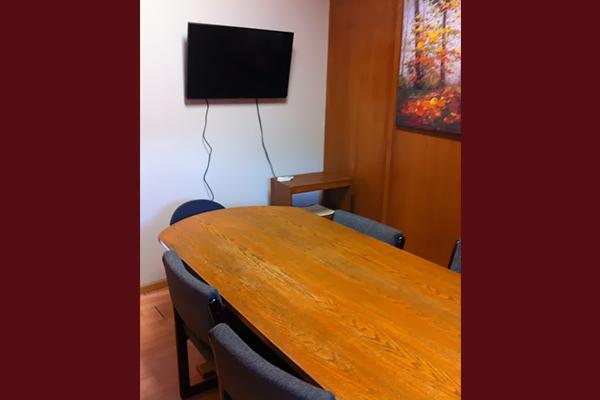 Mesa de madera y pantalla en la pared