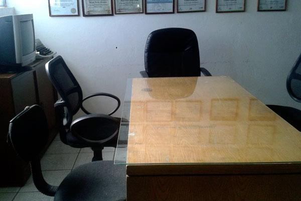 Mesa de madera con vidrio encima y sillas de oficina